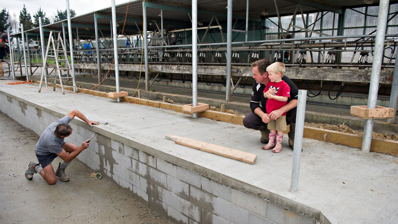 Scott and his son Sam watch as the new dairy shed is built.