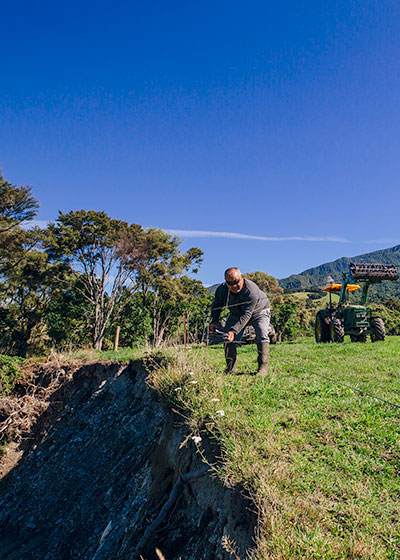 The Hislops' Rockwood Farm 2IC Colin Timms fences along a slip caused by the quake.