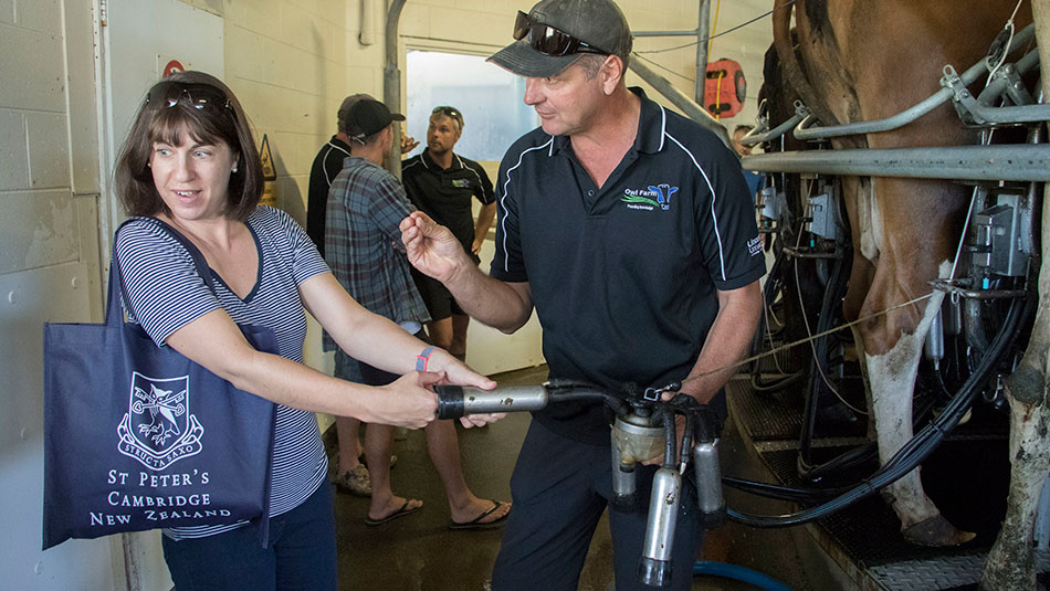 Sarah Morton-Johnson tries out the milking cup on her finger while Doug Storey from Owl Farm explains the technology.